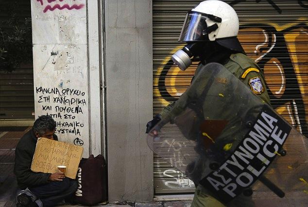 شرطيّ مكافحة شغب يمشي مرورًا بمتسوّل في أثينا (2012)